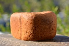 Hot rye bread from the bread machine on wood table Royalty Free Stock Image