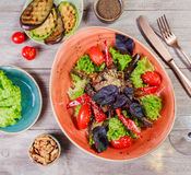 Hot salad with grilled tomatoes, eggplant, zucchini, red pepper, salad leaves, garnished with grated walnuts and basil Royalty Free Stock Image