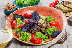 Hot salad with grilled tomatoes, eggplant, zucchini, red pepper, salad leaves, garnished with grated walnuts and basil and glass o Stock Photo