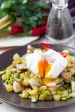 Hot salad with potatoes, ham, peas, mushrooms, poached egg Stock Photography