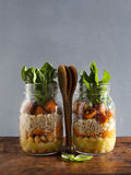 Hot Salad from roasted Pumpkin, Chickpeas, carrots, quinoa, and. Spinach in Mason jars . Healthy Lunch stock image