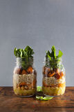 Hot Salad from roasted Pumpkin, Chickpeas, carrots, quinoa, and. Spinach in Mason jars . Healthy Lunch stock photos