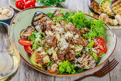 Hot salad with veal, mushrooms, salad leaves, eggplant, zucchini, tomatoes, garnished with grated almonds and Parmesan cheese and Royalty Free Stock Photo