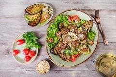 Hot salad with veal, mushrooms, salad leaves, eggplant, zucchini, tomatoes, garnished with grated almonds and Parmesan cheese Royalty Free Stock Photo