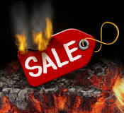 Hot Sale. And liquidation savings concept with a red price tag on fire over burning coals as a consumer symbol of marketing and advertising bargain prices and Stock Photo