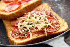 Hot sandwiches. With pepperoni and cheese on frying pan closeup Royalty Free Stock Images