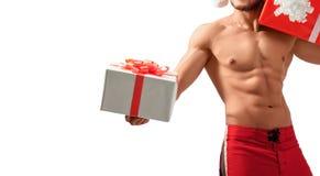 Muscular Santa Claus holding presents Stock Photo