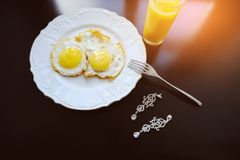 Hot scrambled eggs on a white plate, orange juice. Next are the earrings of the bride. Wedding morning. Bride`s Breakfast stock image