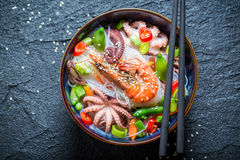 Hot seafood noodle in dark bowl with chopsticks Stock Photography