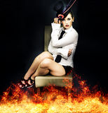 Hot Seat of Entertainment. Woman in theater costume sitting on stage stool with surrounding flames in a edge of your seat performance on the hot seat of Royalty Free Stock Photos