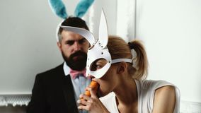 Hot easter couple with rabbit ears. Close up of a girl in a leather rabbit mask who eats carrots against a. Background of bearded man which wears bunny ears stock footage
