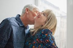 Hot and Sexy Middle-aged Woman Enjoying Kissing of Her Elderly Husband Standing near Opened Window inside Their Home royalty free stock image