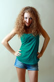 Hot sexy mode. Beautiful Young hot sexy model with curly hair in green top and jeans shorts Royalty Free Stock Photo