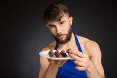 Hot naked handsome man with chocolates, chocolate candies. Smiling naked handsome man wearing dark blue apron holding a white stock photos