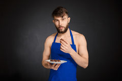 Hot sexy naked handsome man with chocolates, chocolate candies. Stock Photography