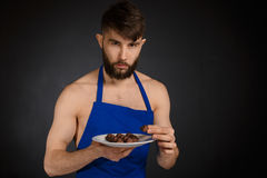 Hot naked handsome man with chocolates, chocolate candies. royalty free stock images
