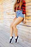 Hot tan slim woman legs in sneakers and jeans shorts - clos Royalty Free Stock Photo