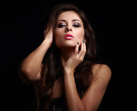 Hot woman in dark touching her makeup Stock Image