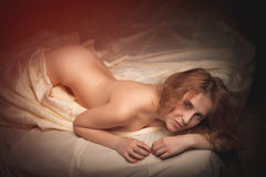 Hot sexy woman with perfect body lying naked in bed Stock Photography