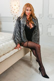 Hot sexy woman in provocative black lingerie bodysuit and fur coat sitting on the bed Royalty Free Stock Photo