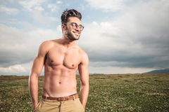 Hot shirtless man posing with his hands in pockets. On a field with grass, looking away from the camera Royalty Free Stock Photography