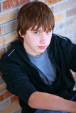 Hot Shot. Handsome teen guy model seated against brick wall Royalty Free Stock Photo