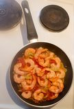 Hot shrimp fried in a pan with herbs royalty free stock photography