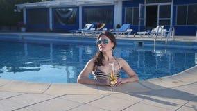 Hot single woman in bikini enjoying cocktail in swimming pool. Stock footage stock footage