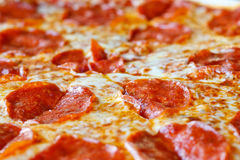 Hot Sliced Pepperoni Pizza. A hot, cheesy, pepperoni pizza sliced and ready to eat Royalty Free Stock Image