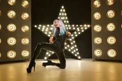 Hot slim woman posing in latex rubber fashion clothes on black background with yellow lights bulbs. Kinky woman in fetish fashion cose catsuit with corset royalty free stock photo