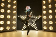 Hot slim woman posing in latex rubber fashion clothes on black background with yellow lights bulbs. Kinky woman in fetish fashion cose catsuit with corset royalty free stock images