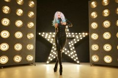 Hot slim woman posing in latex rubber fashion clothes on black background with yellow lights bulbs. Kinky woman in fetish fashion cose catsuit with corset royalty free stock photos