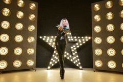 Hot slim woman posing in latex rubber fashion clothes on black background with yellow lights bulbs. Kinky woman in fetish fashion cose catsuit with corset stock image