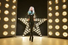 Hot slim woman posing in latex rubber fashion clothes on black background with yellow lights bulbs. Kinky woman in fetish fashion cose catsuit with corset stock photography