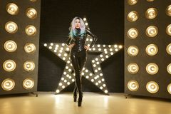Hot slim woman posing in latex rubber fashion clothes on black background with yellow lights bulbs. Kinky woman in fetish fashion cose catsuit with corset royalty free stock image