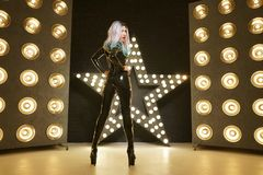 Hot slim woman posing in latex rubber fashion clothes on black background with yellow lights bulbs. Kinky woman in fetish fashion cose catsuit with corset stock images