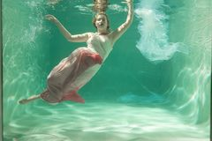 Hot Slim Woman Posing Under water in beautiful clothes alone in the deep. Awesome royalty free stock image