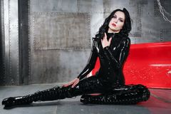Fashionable caucasian brunette girl wearing black latex catsuit and posing inside grey room with metall walls alone. pretty hot wo. Hot slim young woman in latex stock photography