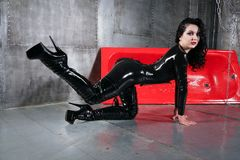 Fashionable caucasian brunette girl wearing black latex catsuit and posing inside grey room with metall walls alone. pretty hot wo. Hot slim young woman in latex royalty free stock image
