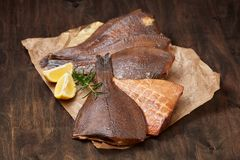 Hot smoked beheaded flounder on the crumpled paper Stock Photos