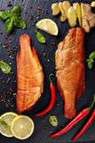 Hot smoked red snappers on a black stone. Plate with spices, herbs and sliced lemons, vertical view from above stock photography