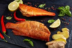 Hot smoked red snappers, top view. Hot smoked red snappers on a black stone plate with spices, herbs and sliced lemons, view from above, close-up royalty free stock photography