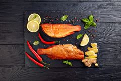 Hot smoked red snappers, top view. Hot smoked red snappers on a black stone tray with spices, herbs and sliced lemons, view from above, flatlay royalty free stock photos