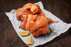 Hot smoked salmon fillet rolls on crumpled paper. With lemon and greens royalty free stock image