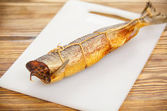 Hot smoked salmon fish on kitchen board on table royalty free stock photography