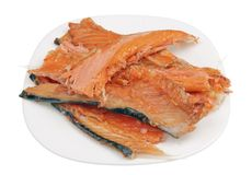 Hot smoked   salmon trim and leftovers with bones and fins low cost delicacy on plate isolated. Hot smoked   salmon trim and leftovers with bones and fins low royalty free stock images