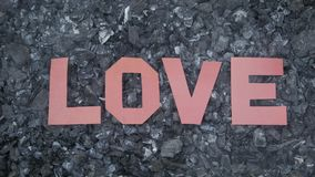 On the hot, Smoking coals, the inscription love is made of letters cut out of paper.