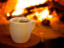 Hot smoking coffee by fireplace Royalty Free Stock Photos