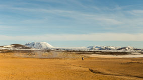 Hot soil in geothermic area surrounded by snowy mountains in North Iceland. Hot springs and boiling mud pits of a geothermic area contrast with snowy mountains Royalty Free Stock Photos