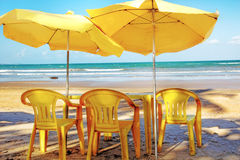 Hot sommer day, relaxing at the beach. View at the beach, sitting  behind three yellow chairs, a  tables and two sunshades Stock Photography